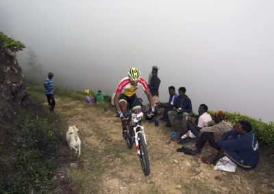 Mountain biking passed tea plantation workers in the cloud in Sri Lanka