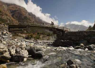 Mountain biker cycling over the wooden bridge along the Attack the Pass route